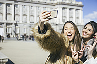 Spain, Madrid, two happy women taking a selfie with smartphone in front of royal palace - ABZF000263