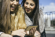 Two happy women looking at smartphone - ABZF000266