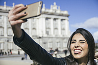 Spain, Madrid, portrait of woman making faces while taking a selfie with smartphone - ABZF000269