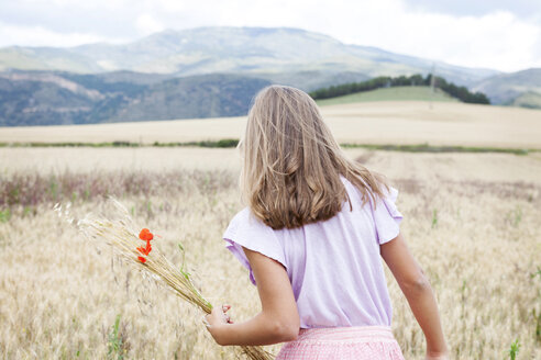 Spain, Girona, back view of girl picking flowers on a meadow - VABF000302