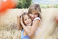 Spain, Girona, portrait of two happy sisters hugging each other on a meadow - VABF000305