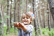 Portrait of smiling little boy wearing paper crown catching confetti - VABF000335