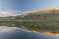 Italy, Abruzzo, Gran Sasso e Monti della Laga National Park, plateau Campo Imperatore, Reflection on lake Petranzoni at sunset - LOMF000232