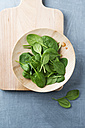 Wooden bowl of spinach leaves on wooden board - MYF001381