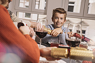Boy pulling ends of Christmas crackers at family table - MFF002833