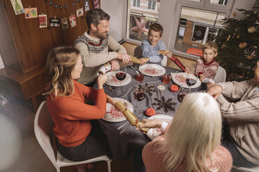 Happy family of three generations pulling at ends of Christmas crackers before dinner - MFF002836