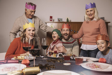 Funny three-generation family portrait with paper crowns during Christmas dinner - MFF002842