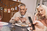 Annoyed senior woman with husband using smartphone after Christmas dinner - MFF002857