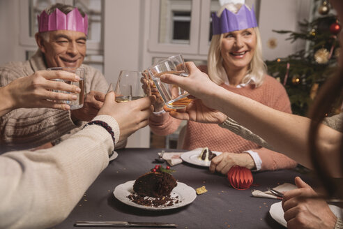 Happy senior couple with paper crowns clinking glasses while having Christmas pudding with their family - MFF002866