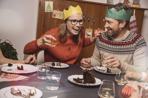 Happy couple with paper crowns laughing while having Christmas dinner - MFF002869