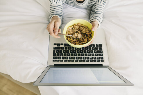 Woman in bed with laptop and muesli bowl - EBSF001238