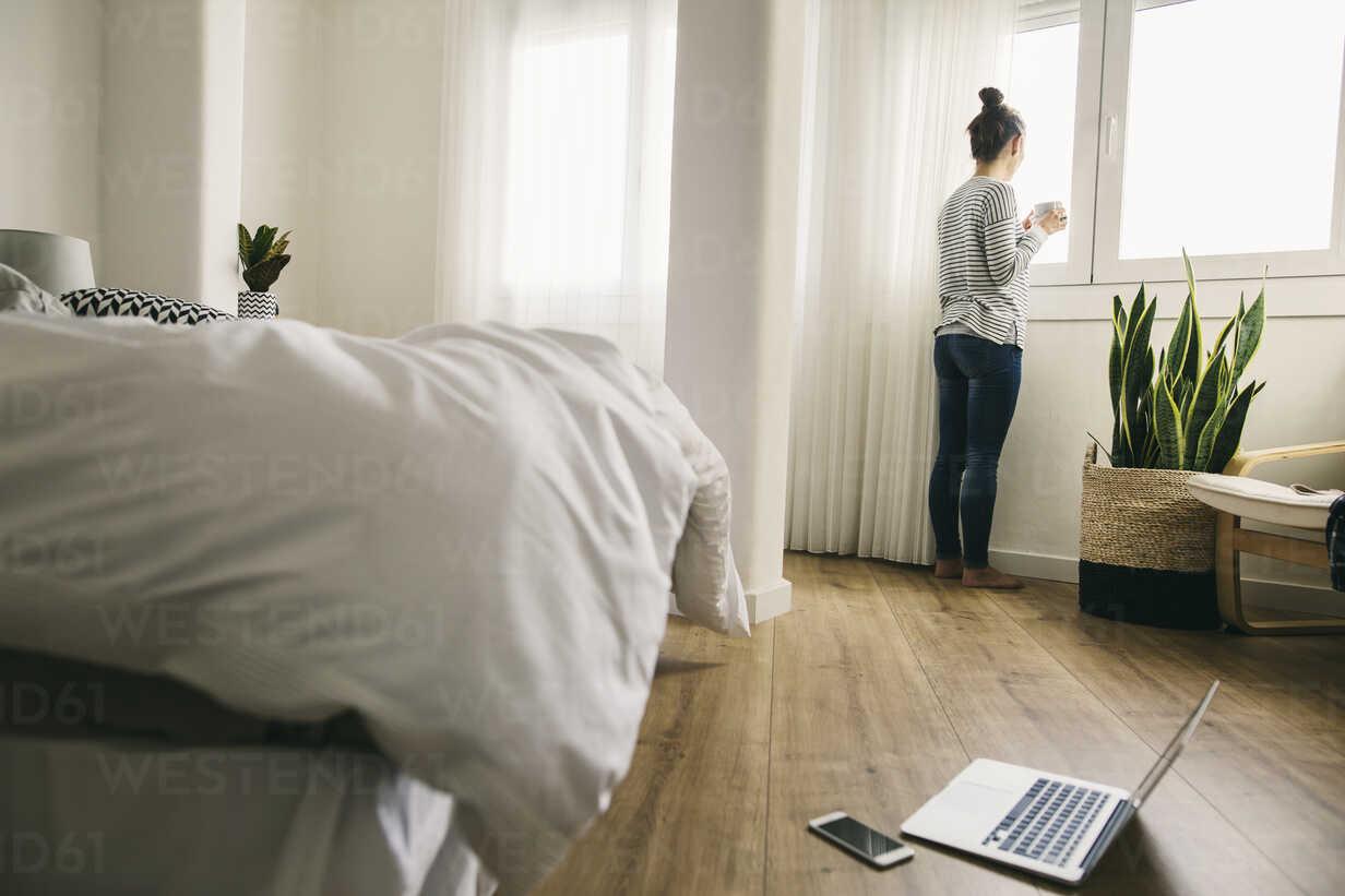 Woman looking out of bedroom window - EBSF001241 - Bonninstudio/Westend61