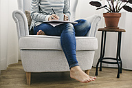 Woman sitting in armchair writing on notepad - EBSF001244