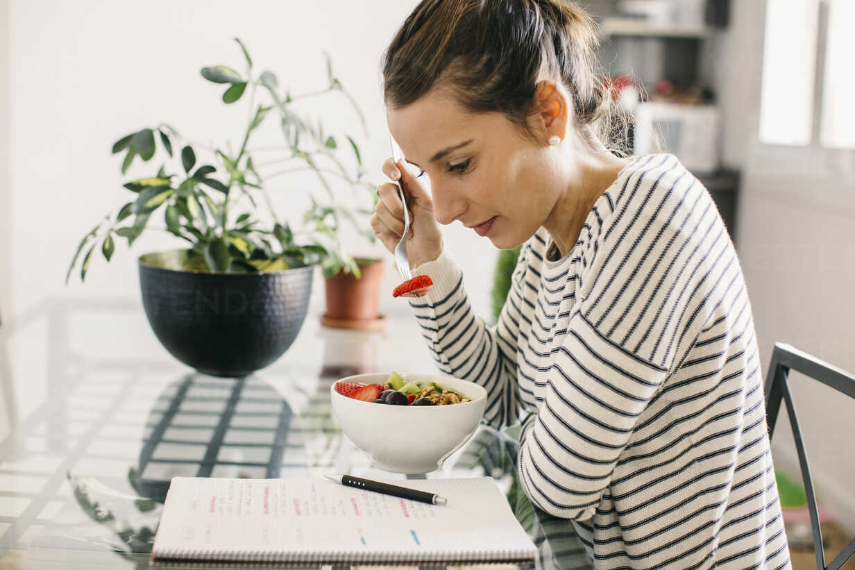 Woman sitting at table with fruit muesli looking at notepad - EBSF001247 - Bonninstudio/Westend61