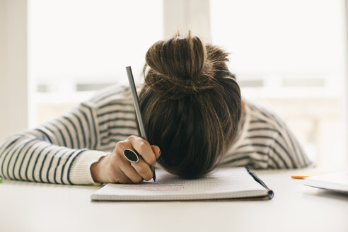 Woman writing on notepad resting her head on table - EBSF001250
