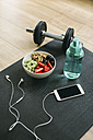 Dumbbell, drinking bottle, fruit bowl and smartphone with earphones - EBSF001259