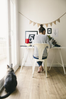 Woman working in home office with cat looking out of window - EBSF001271