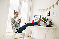 Woman at home laying feet on table looking at cell phone - EBSF001277