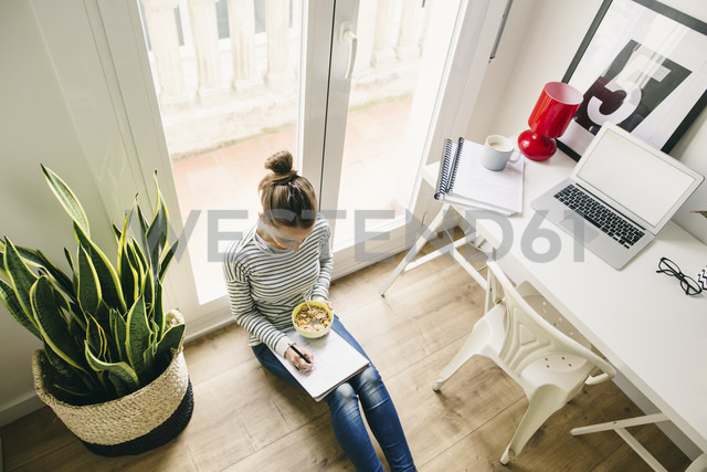 Woman sitting on floor writing on notepad - EBSF001280 - Bonninstudio/Westend61
