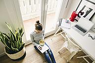 Woman sitting on floor writing on notepad - EBSF001280