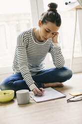 Woman sitting on floor with muesli bowl writing on notepad - EBSF001286