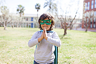 Portrait of little boy dressed up as a superhero standing on a meadow - VABF000346