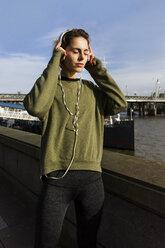 UK, London, female runner listening music at riverwalk - BOYF000130