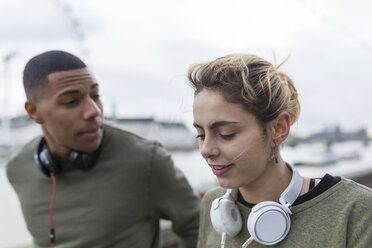 Young couple with headphones outdoors - BOYF000145