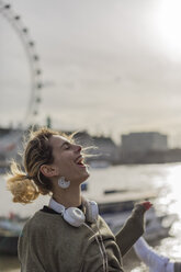 UK, London, laughing woman with headphones at River Thames - BOYF000151
