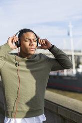 UK, London, man listening music at riverwalk - BOYF000157