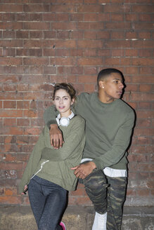 Stylish young couple leaning against brick wall at night - BOYF000160