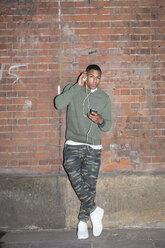 Young man listening music at brick wall at night - BOYF000163