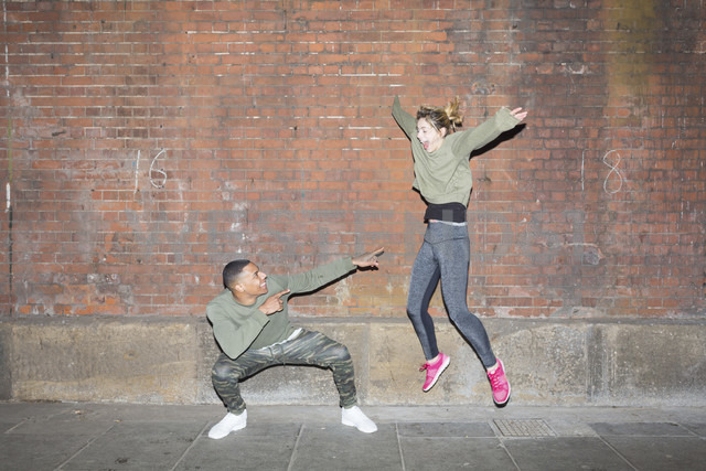 Playful young couple in front of brick wall at night - BOYF000166