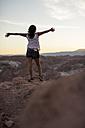 Chile, San Pedro de Atacama, woman in the Atacama desert with outstretched arms - MAUF000344