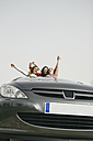 Women having fun and laughing in a convertible car - ABZF000281