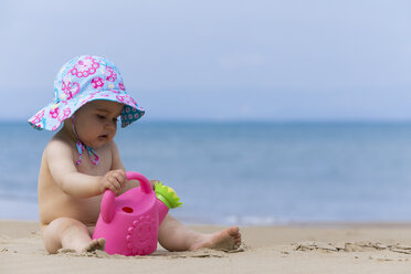 Naked little baby girl wearing summer hat playing on the beach with toy watering can - DSF000643