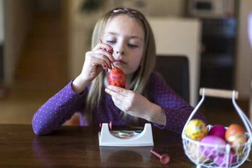 Girl painting Easter egg at home - SARF002630