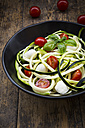 Bowl of zucchini spaghetti with mozzarella, cherry tomatoes and basil on wood - LVF004637