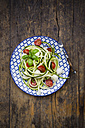 Bowl of zucchini spaghetti with mozzarella, cherry tomatoes and basil on wood - LVF004640