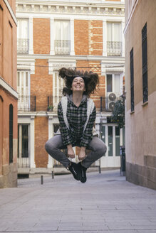 Spain, Madrid, happy young woman jumping in the air in a street - ABZF000288