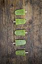 Row of homemade kiwi ice lollies on dark wood - LVF004643