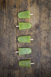 Row of homemade kiwi ice lollies on dark wood - LVF004643