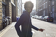 Young man listening to music on urban street - BOYF000188