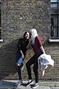 Two female best friends whispering at brick building - BOYF000194