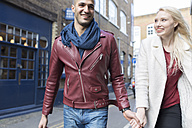 Young couple walking hand in hand on urban street - BOYF000197
