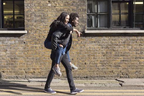 Young man carrying girlfriend piggyback at brick building - BOYF000203