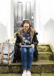 London, student girl with headphone and writing pad - MGOF001521