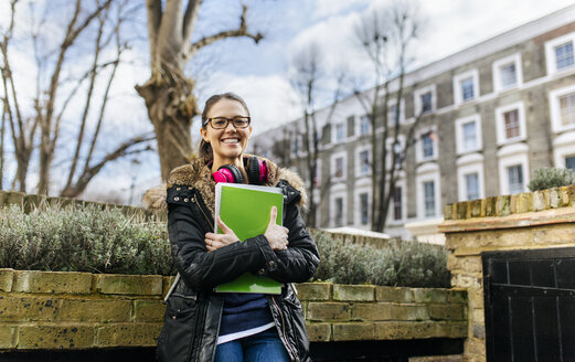 London, student girl with headphone and writing pad, language holiday - MGOF001524