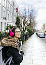 London, student girl with headphone and writing pad - MGOF001527