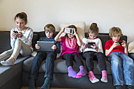 Group picture of five children sitting on one couch using different digital devices - SARF002642